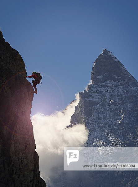 Silhouette einer Bergsteigerin beim Klettern an einer Felswand in der Nähe des Matterhorns  Kanton Wallis  Schweiz