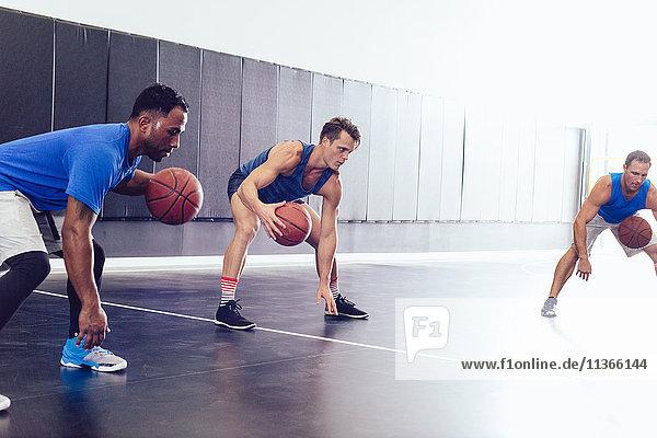 Männliche Basketballmannschaft beim Aufwärmen auf dem Basketballplatz