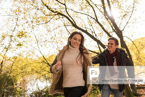 Young couple running in forest  laughing
