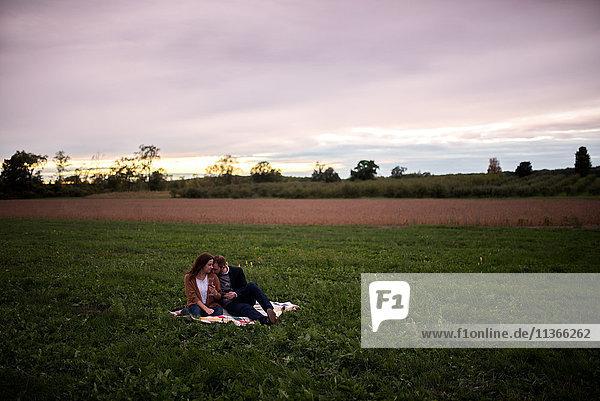 Romantisches Paar entspannt sich bei Sonnenuntergang auf einer Picknickdecke im Feld