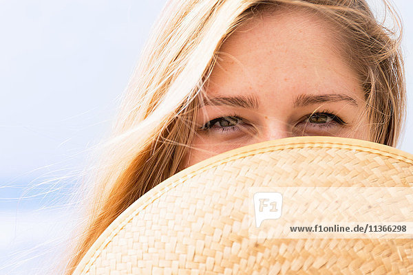 Junge Frau bedeckt Gesicht mit Hut