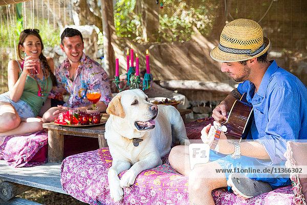 Freunde in Pergola beim Gitarrespielen