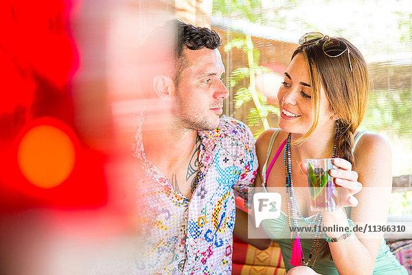 Paar sitzt zusammen in einer Pergola und geniesst ein Getränk