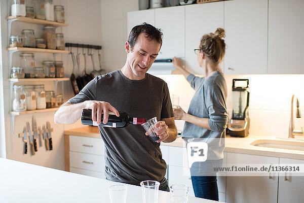 Mittleres erwachsenes Paar gießt Rotwein in die Küche