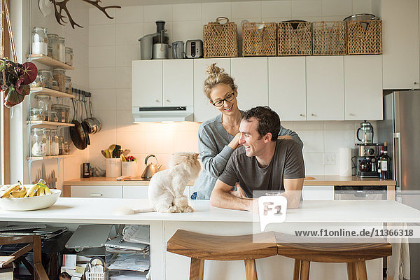 Mittleres erwachsenes Paar mit Katze am Küchentisch
