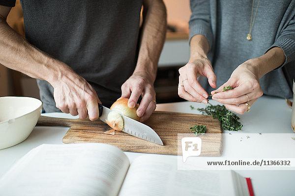 Mittelteil des Paares beim Zwiebelschneiden in der Küche