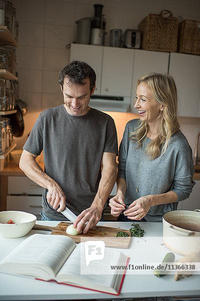 Mittleres erwachsenes Paar beim Zwiebelschneiden in der Küche