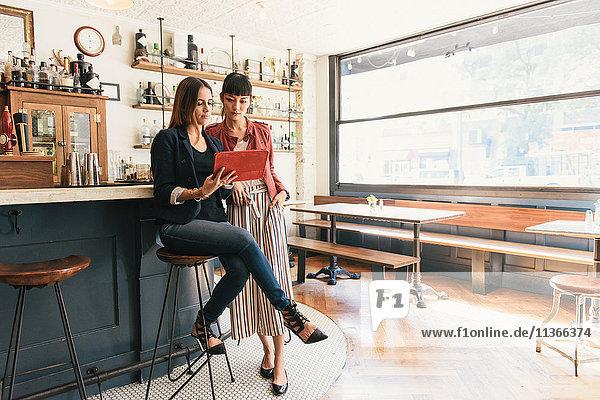 Zwei junge Frauen schauen sich digitales Tablett in der Cocktailbar an