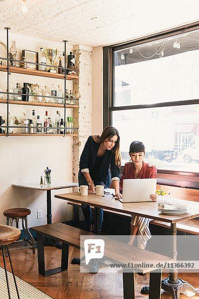 Zwei junge Kundinnen schauen im Restaurant auf den Laptop