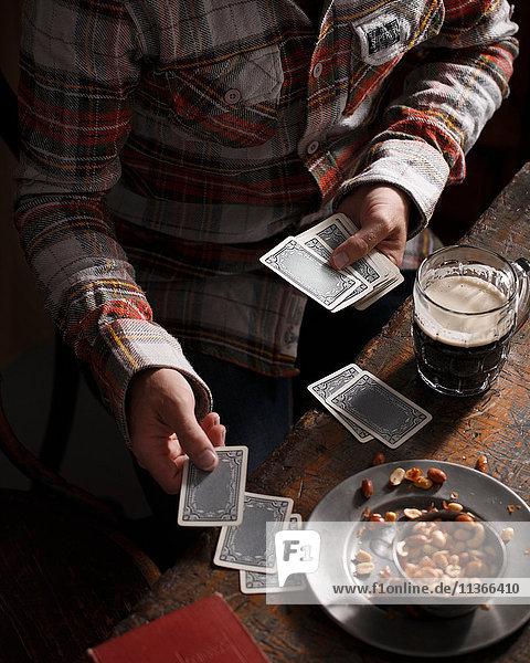 Geschnittener Schuss eines Mannes  der am Kneipentisch Karten spielt