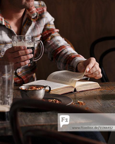 Geschnittener Schuss eines Mannes  der Bier trinkt und am Kneipentisch ein Buch liest