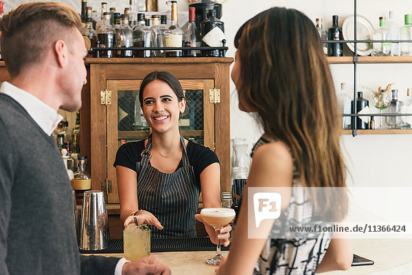 Waitress serving young couple in cocktail bar