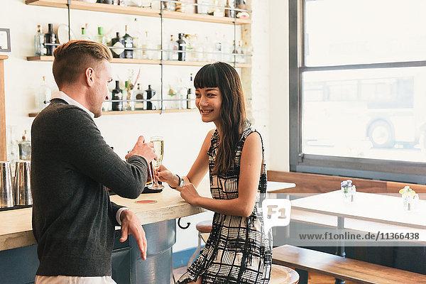 Junges Paar stösst in der Cocktailbar an
