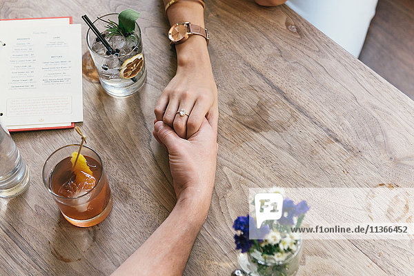 Romantic young couple holding hands over restaurant table