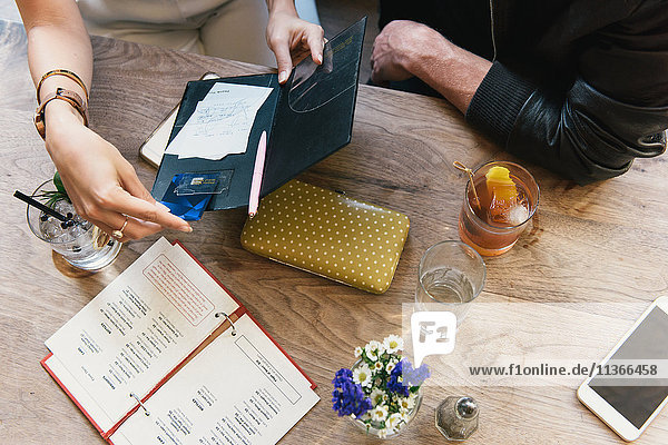 Young woman opening bill at cocktail bar table