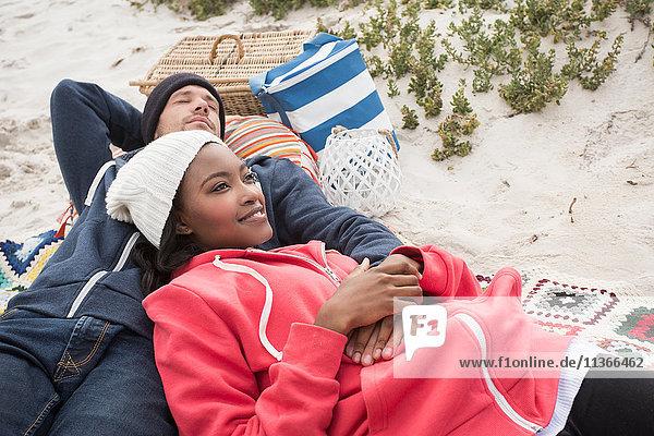 Junges Paar liegt auf einer Picknickdecke am Strand  Western Cape  Südafrika
