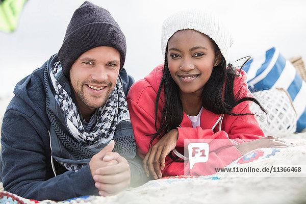 Porträt eines jungen Paares auf einer Picknickdecke am Strand liegend  Western Cape  Südafrika