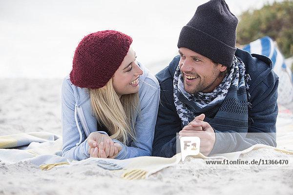 Junges Paar liegt auf einer Picknickdecke und unterhält sich am Strand  Western Cape  Südafrika