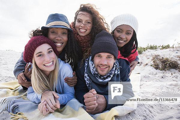 Porträt übereinanderliegender junger erwachsener Freunde am Strand  Western Cape  Südafrika