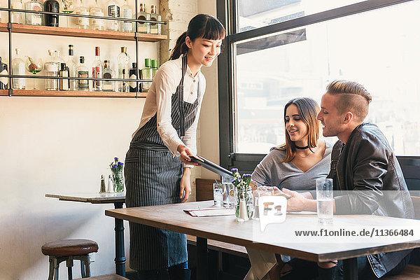 Weiblicher Barkeeper übergibt Rechnung an junges Paar am Cocktail-Bar-Tisch