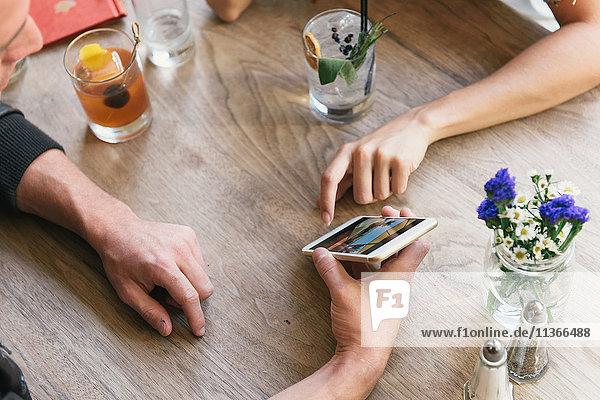 Junges Paar zeigt am Cocktail-Bar-Tisch auf ein Smartphone