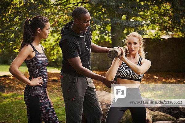 Zwei Frauen mit Personal Trainerin erklären Baumstamm Schulterheben im Park