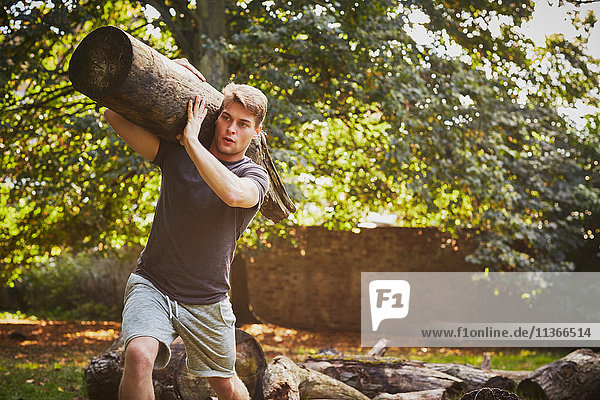 Young man training  lifting tree trunk on shoulder in park