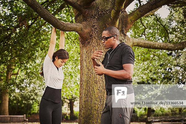 Personal Trainerin  die die Frau mit Hilfe eines Parkbaumzweiges in Pull-Ups unterweist.