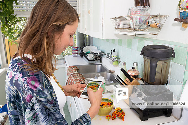 Woman photographing bowl of food with smartphone