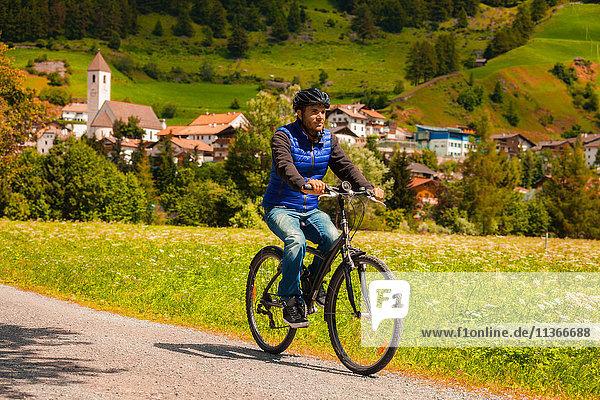 Mittlerer Erwachsener Mann radelt auf Dorfpfad im Vinschgau  Südtirol  Italien