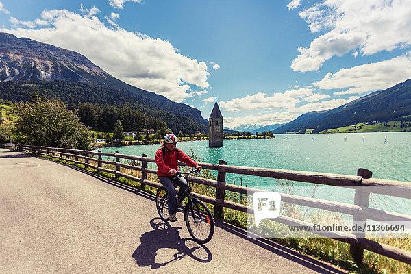 Ältere Frau radelt am See mit Curon-Glockenturm  Vinschgau  Südtirol  Italien