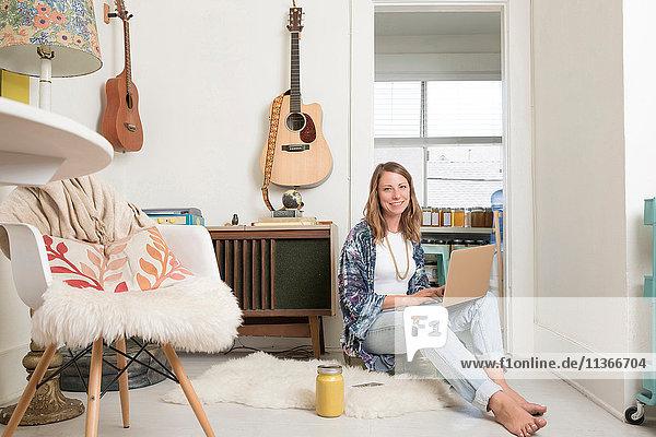 Frau sitzt mit Laptop im Wohnzimmer