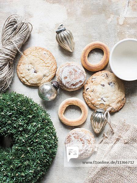 Draufsicht auf silberne Weihnachtskugeln und frische Kekse und Bagels