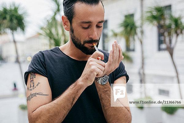 Mid adult man lighting cigarette