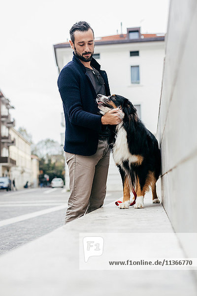 Mid adult man petting dog on wall in city