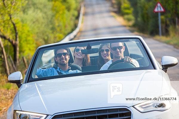 Vier erwachsene Freunde fahren auf einer Landstraße in einem Cabriolet  Mallorca  Spanien