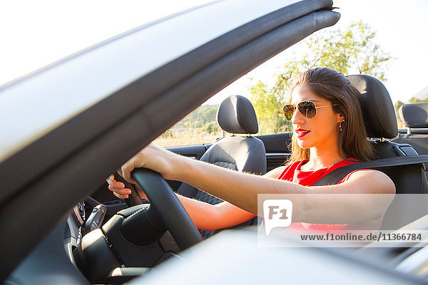 Young woman driving on rural road in convertible  Majorca  Spain