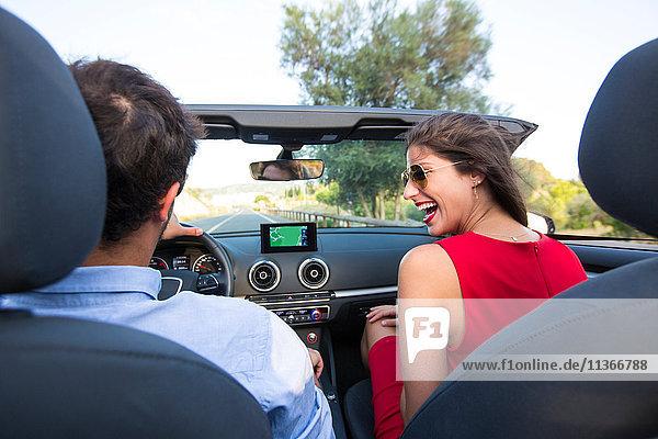 Junges Paar lacht während einer Fahrt auf der Landstraße im Cabriolet  Mallorca  Spanien