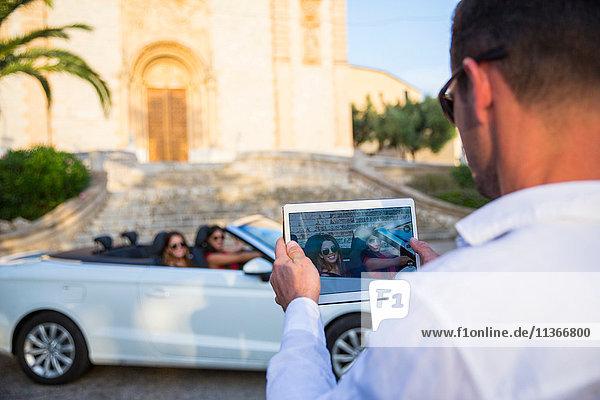 Über-Schulter-Ansicht eines Mannes  der zwei junge Touristinnen im Cabriolet fotografiert  Calvia  Mallorca  Spanien