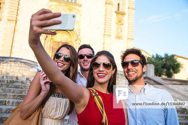 Zwei Touristenpaare mit Sonnenbrillen beim Selfie vor der Kirche  Calvia  Mallorca  Spanien