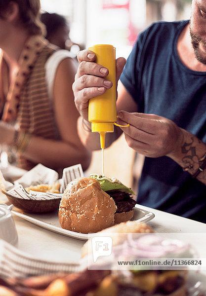Cropped shot of couple putting mayonnaise on burger at sidewalk cafe