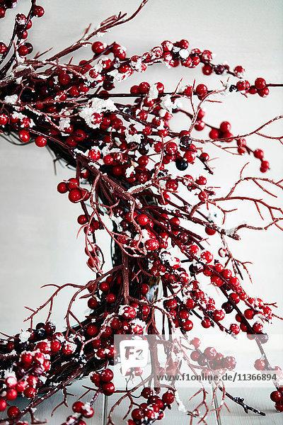 Ausgeschnittener Schuss eines Zweigs und roter Beeren-Weihnachtskranz