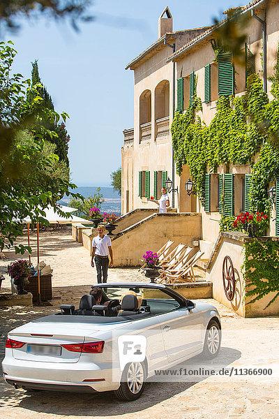 Pförtner empfängt Paar  das mit einem Cabrio zum Boutique-Hotel fährt  Mallorca  Spanien