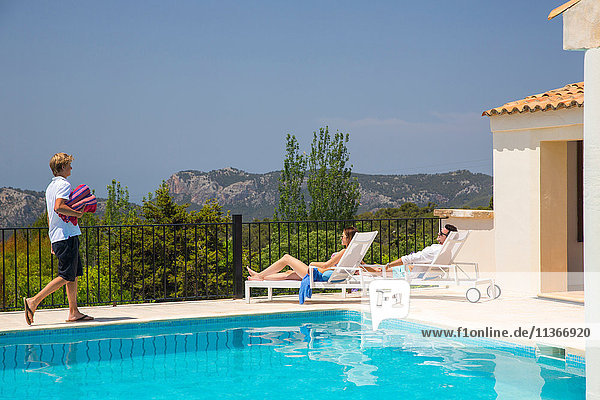 Waiter carrying towels for guest couple by boutique hotel swimming pool  Majorca  Spain