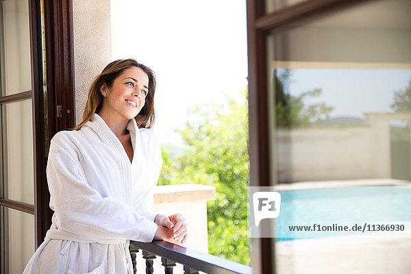 Junge Frau schaut aus dem Fenster einer Boutique-Hotelsuite  Mallorca  Spanien