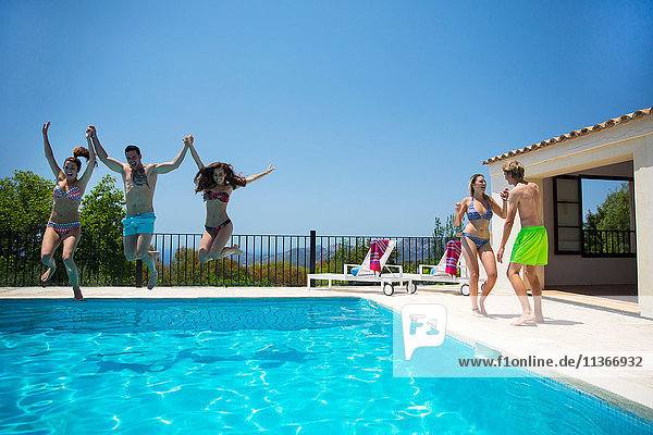 Young women and man jumping together into boutique hotel swimming pool  Majorca  Spain