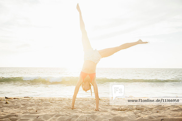 Frau am Strand beim Handstand