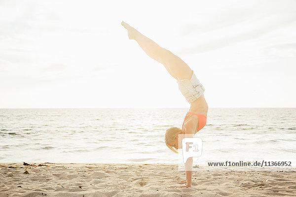 Woman on beach doing handstand