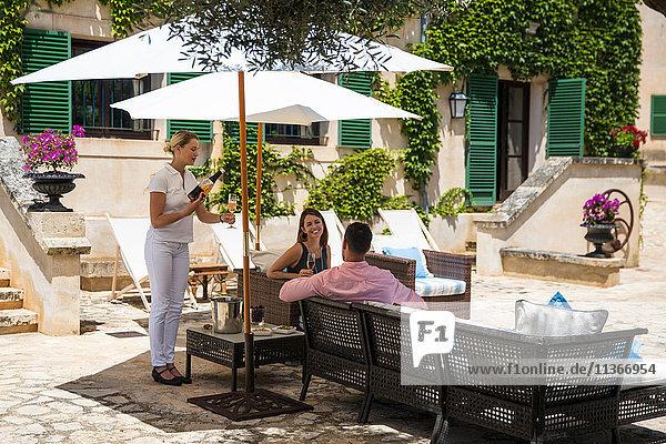 Kellnerin eines Boutique-Hotels serviert Champagner für Paare auf der Terrasse  Mallorca  Spanien