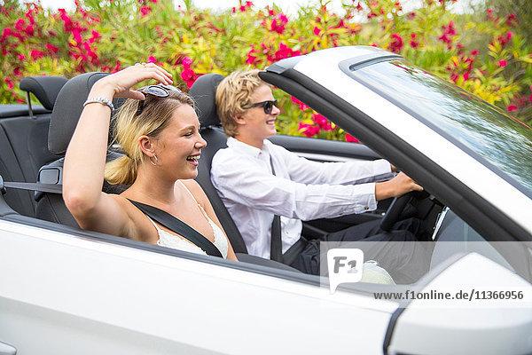 Junges Paar fährt Cabriolet an Blüten vorbei  Mallorca  Spanien